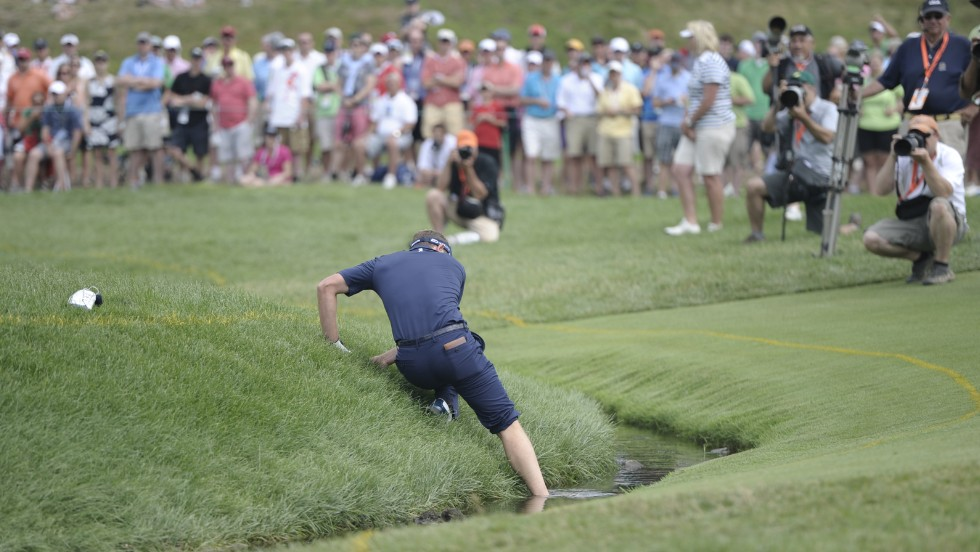 Luke Donald climbs up a bank after hitting out of a water hazard at the 4th hole on June 16.