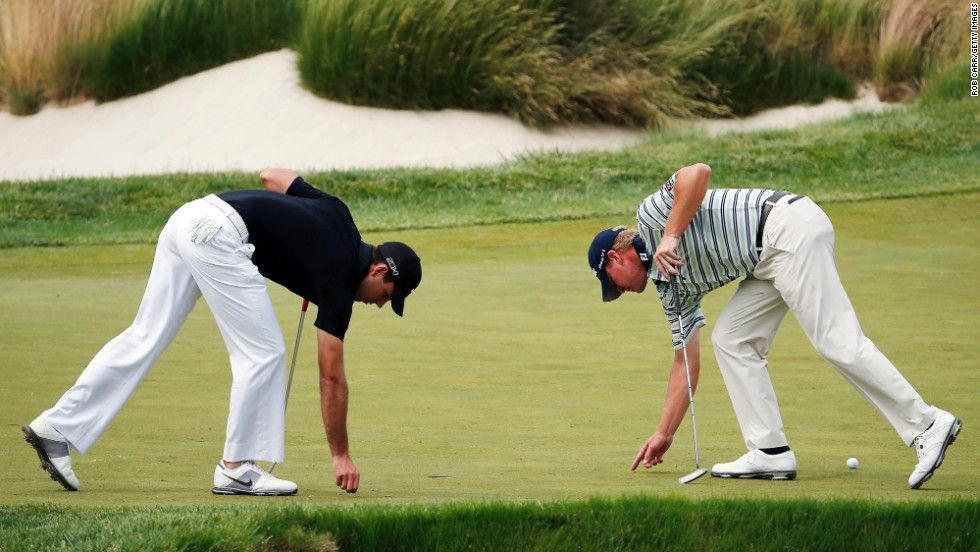 Charl Schwartzel and Steve Stricker examine the green during the final round.