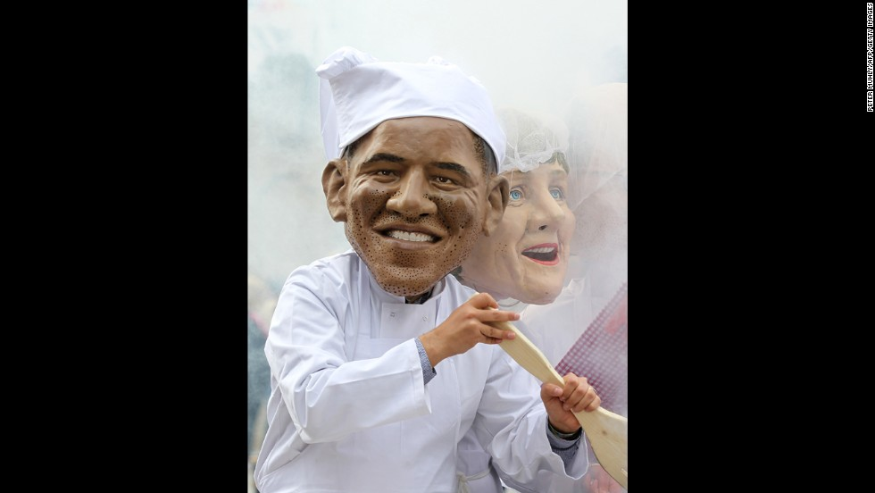 An Oxfam charity volunteer wearing an Obama head stirs a cauldron on June 16.