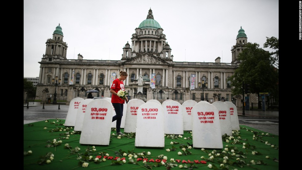 An Oxfam worker walks between mock gravestones on June 17 in Belfast. The gravestones represent the thousands of people killed in Syria's civil war.