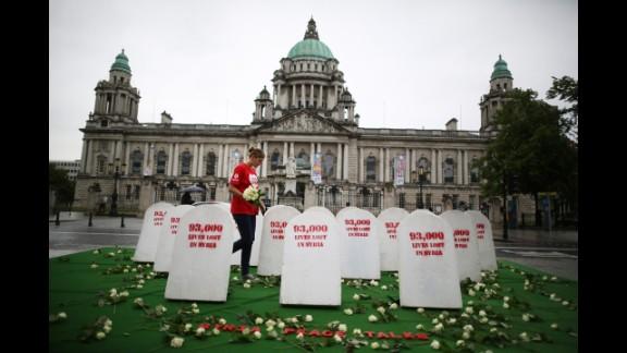 An Oxfam worker walks between mock gravestones on June 17 in Belfast. The gravestones represent the thousands of people killed in Syria's civil war.