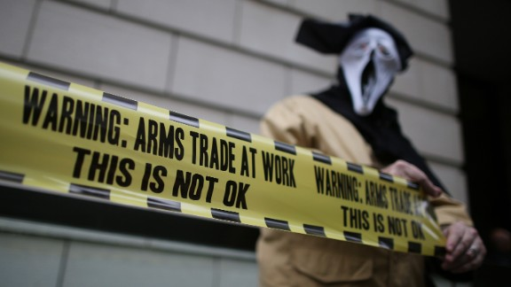 A masked demonstrator protests outside arms manufacturer BAE Systems on Wednesday, June 12, in London.