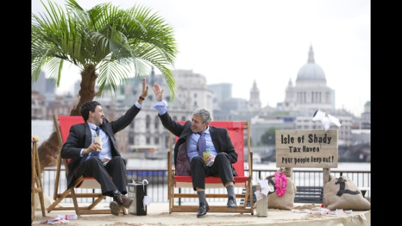"""Protesters in suits high-five on the set of their """"Isle of Shady Tax Haven"""" in London on Friday, June 14."""