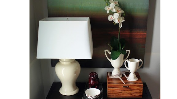 Shannon Smith's foyer in Charlotte, North Carolina, is very small and not well-defined, so she chose a tall painting and an orchid to set her space apart from the living room.