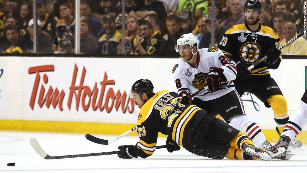 Chris Kelly of the Boston Bruins falls to the ice going for the puck against Ben Smith of the Chicago Blackhawks.