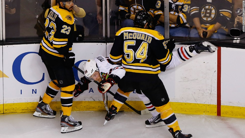 Ben Smith of the Chicago Blackhawks is upended along the boards by Chris Kelly, left,  and Adam McQuaid, right, of the Boston Bruins.