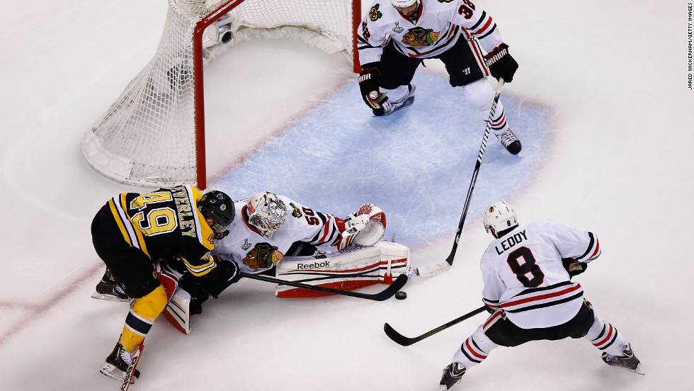 Corey Crawford of the Chicago Blackhawks makes a save against Rich Peverley of the Boston Bruins.