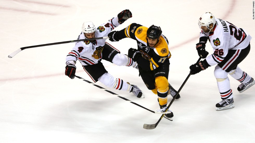 Milan Lucic of the Boston Bruins skates after the puck against Niklas Hjalmarsson, left, and Michal Handzus of the Chicago Blackhawks.