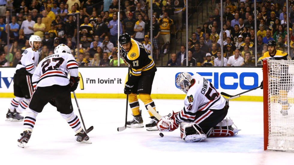 Corey Crawford of the Chicago Blackhawks attempts to make a save against Milan Lucic of the Boston Bruins.