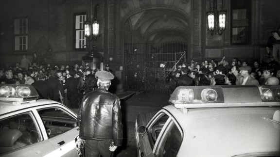 Crowds gather outside of the Central Park West apartment building, the Dakota, after news of Lennon