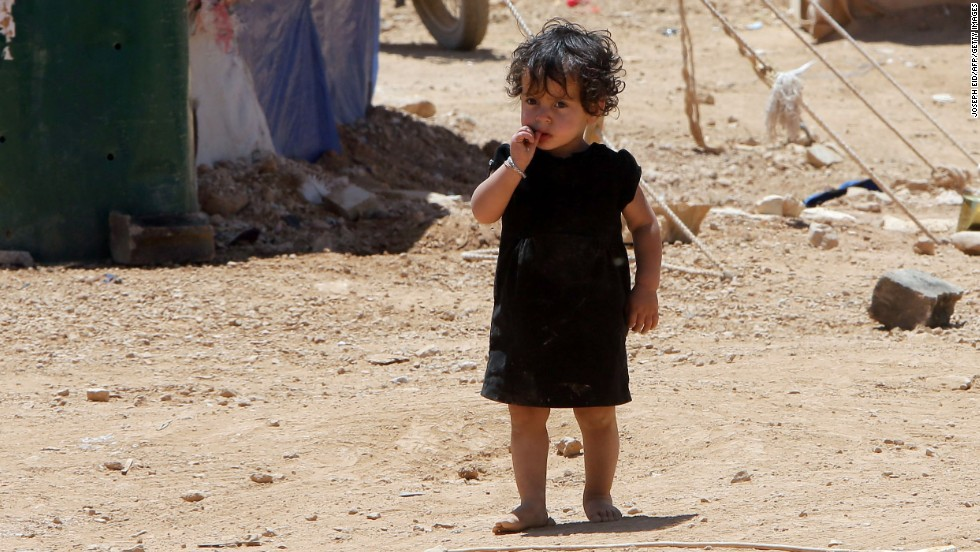 A child whose family fled violence in Syria stands at the Arsal refugee camp in Lebanon in June 2013.