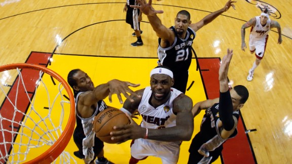 LeBron James of the Miami Heat goes up for a shot against Kawhi Leonard, left, Tim Duncan and Danny Green, right, of the San Antonio Spurs in the first half.