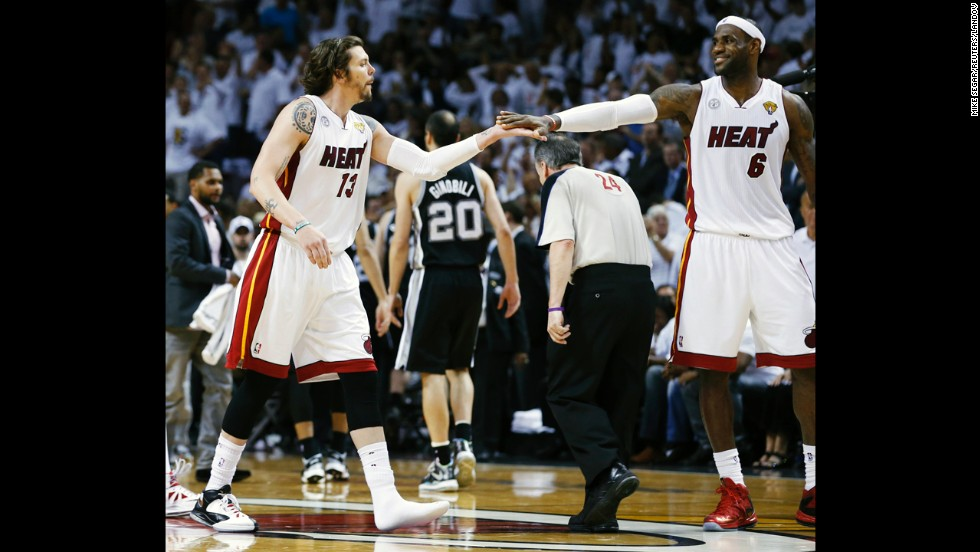 The Miami Heat's LeBron James, right, congratulates teammate Mike Miller after he hit a three-point basket wearing one shoe during the fourth quarter against the San Antonio Spurs.