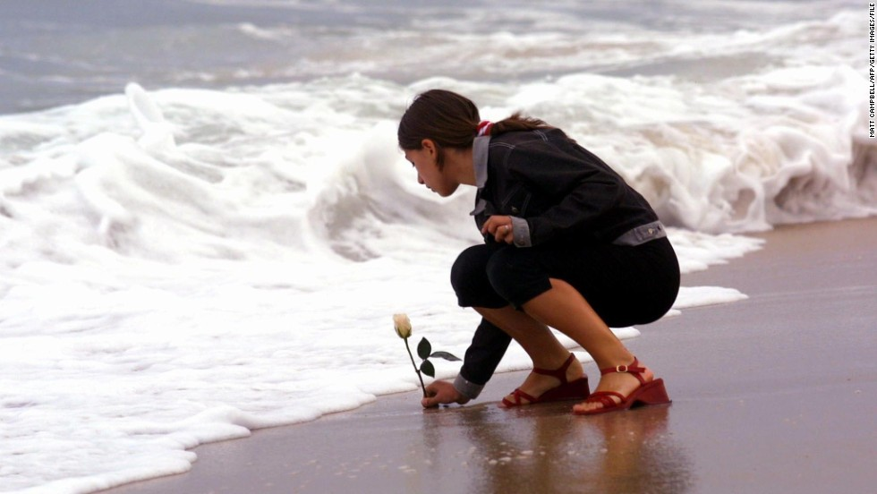 Antonella Naglieri, whose relatives Giuseppe Mercurio and Anna D'Alessandro were killed in the crash, places a rose in the surf after a memorial service at Smith Point Park in Shirley, New York, on July 17, 2001.