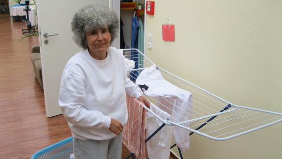Martha Hütter, a resident at the shared apartment in Potsdam, hangs out the washing. Residents suffer from dementia, but everyone is encouraged to contribute to the household chores.