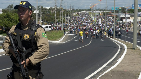 A police officer holds his weapon as protesters continue their demonstration ahead of Brazil