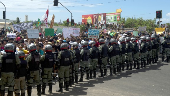 Protesters confront riot police officers on the distant outskirts of the Castelao Stadium, which has been newly built for next year