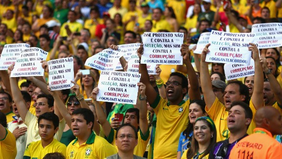 Fans hold up banners - which state that they are protesting against corruption, rather than the national team - ahead of Brazil