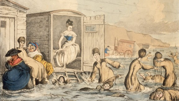 """In 1825, women wore """"bathing dresses"""" at the beach. This illustration shows women of the era venturing into the ocean via bathing machines -- sort of a dressing room on wheels -- that brought them directly to the water."""