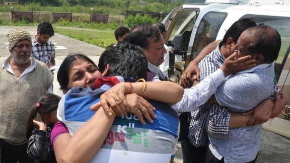 Evacuees hug their family members after arriving by helicopter in Dehradun, the capital of the state of Uttarakhand on June 19.