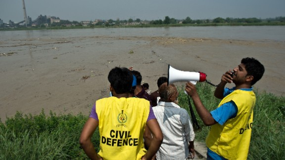 Civil Defence volunteers warn people against attempting to catch floating pumpkins, watermelons and other objects from the rising waters of the Yamuna River in New Delhi on June 19.