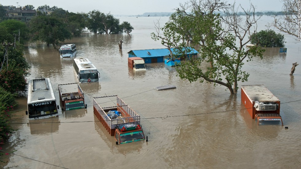 Buses and trucks are submerged in the rising waters of the Yamuna River near the Tibetan market in New Delhi on June 19.