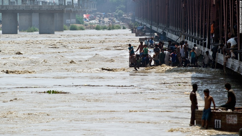 Men watch the rising waters of the Yamuna River from a bridge in New Delhi on June 19.