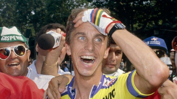 Greg LeMond celebrates his remarkable triumph in the 1989 Tour as he edged out Fignon by just eight seconds having won the final time trial stage into Paris using then revolutionary tri bars.