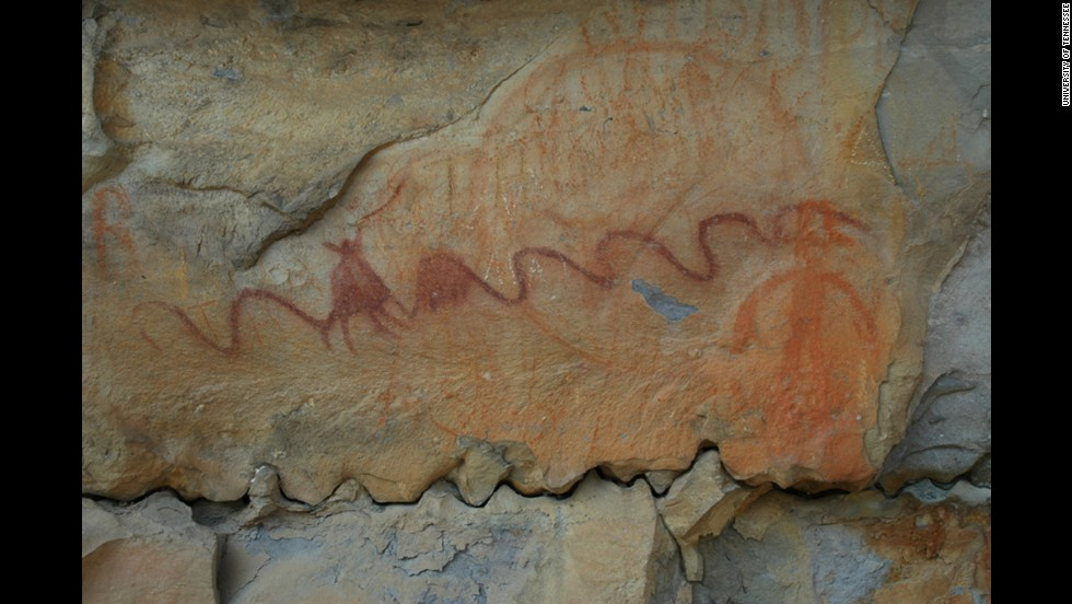 An ancient Native American pictograph found on a rock in northern Alabama features a long curving line and a faded circle behind.