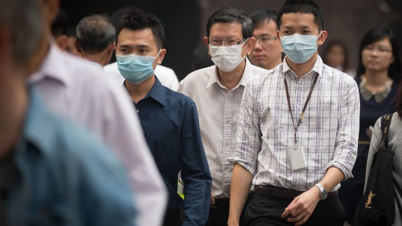 Masked pedestrians crossed a street in the central business district on June 20.