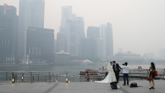 Undeterred by the smog, a couple took engagement photographs in front of the city