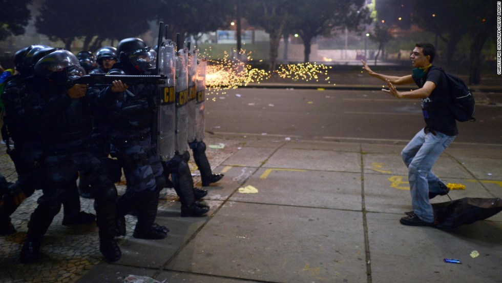 "Police fire rubber bullets at a protester during clashes in Rio de Janeiro on Thursday, June 20. Demonstrations in Brazil began in response to <a href=""http://www.cnn.com/2013/06/20/world/americas/brazil-protests/?hpt=hp_t2"">plans to increase fares for the public transportation system</a> but have broadened into wider protests over economic and social issues. Since then, both Sao Paulo and Rio de Janeiro have agreed to roll back prices on bus and metro tickets.<br />"