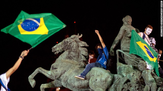 Demonstrators stand on a statue in Niteroi, outside of Rio de Janeiro, on Wednesday, June 19.