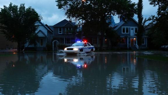 A police car patrols a flooded Calgary neighborhood that was evacuated on June 20.