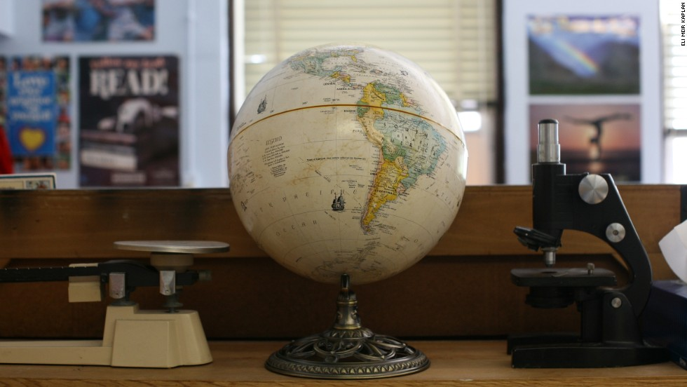 A scale, globe and microscope sit on a desk in a classroom at St. Jerome Academy.