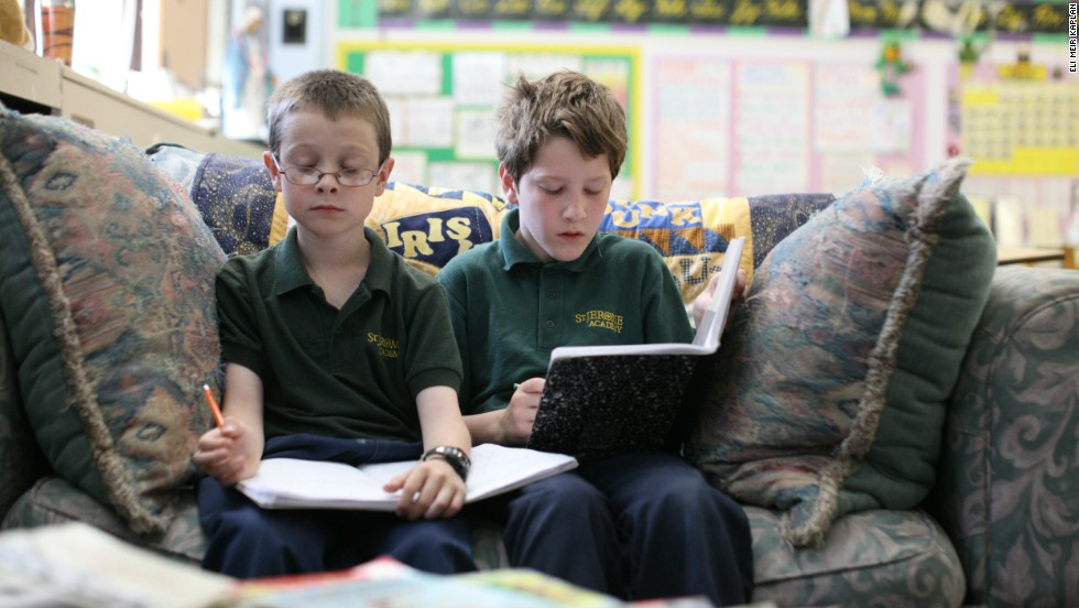 "Fourth-grade students read together in literature class at St. Jerome Academy. The school's curriculum describes how the ""building blocks of learning"" can be used in ""the shape of the soul."""