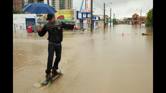 A man longboards through a flooded downtown street in Calgary on Friday, June 21.