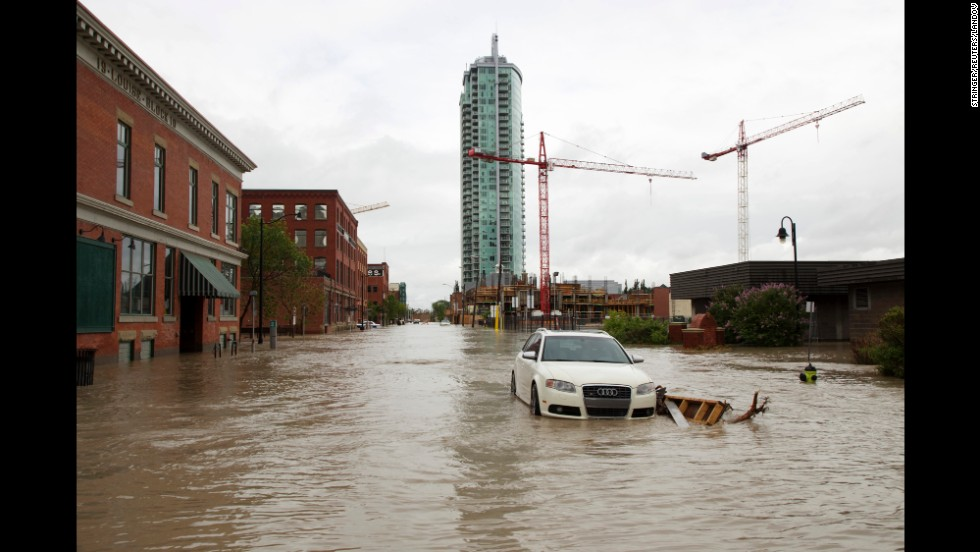 A car sits on a flooded street in Calgary on June 21.