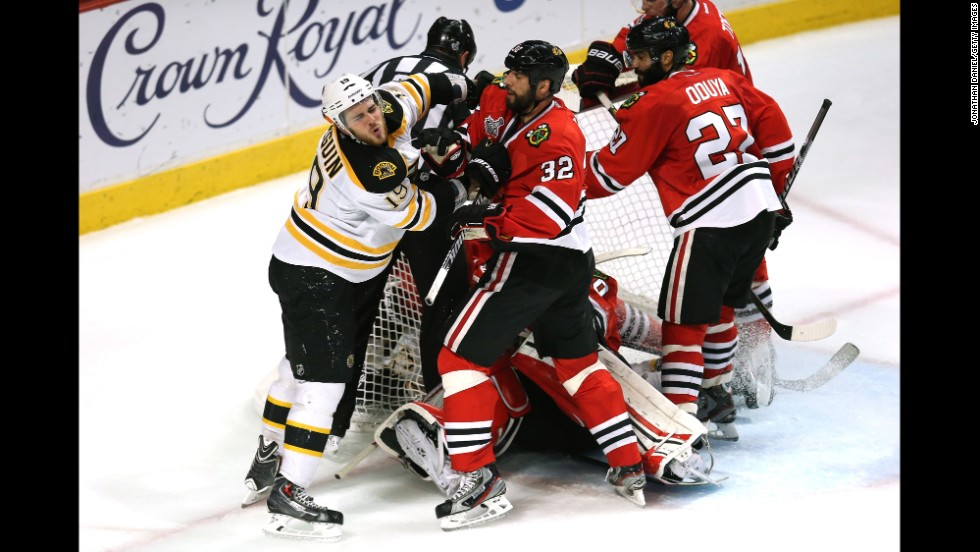 Tyler Seguin of the Bruins and Michal Rozsival of the Blackhawks push each other in front of the net.