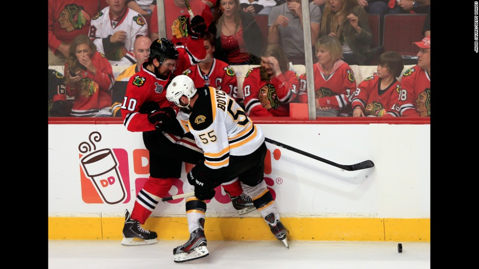 Patrick Sharp of the Chicago Blackhawks pushes Johnny Boychuk of the Boston Bruins along the boards.