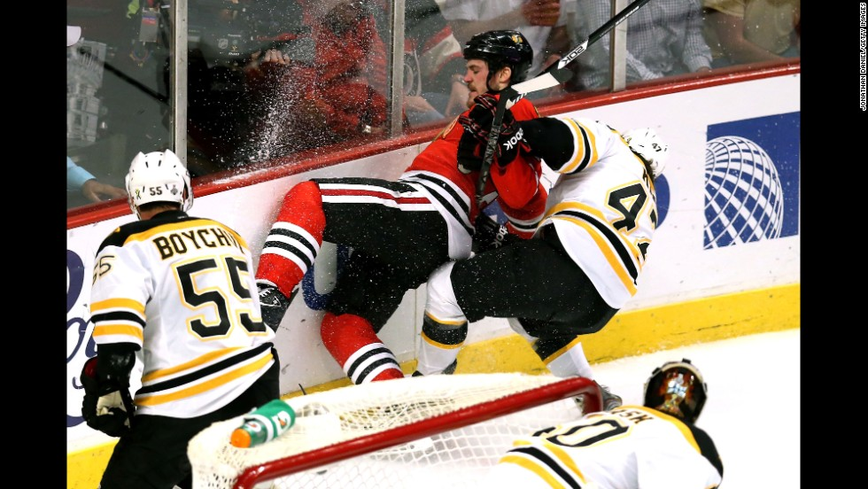 Andrew Shaw of the Chicago Blackhawks is pulled down by Torey Krug of the Boston Bruins.