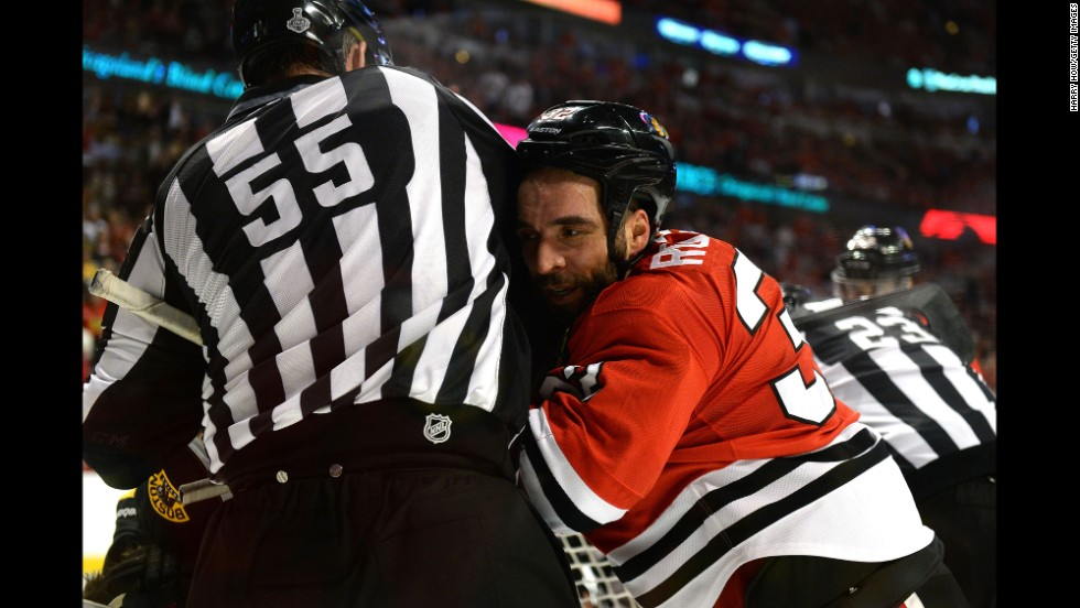 Michal Rozsival of the Chicago Blackhawks is pushed into linesman Shane Heye.