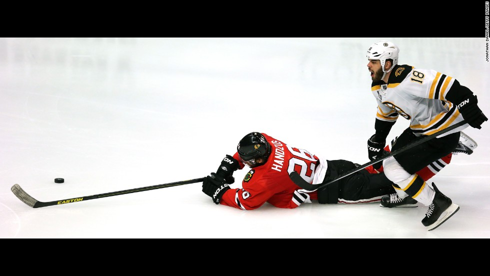 Michal Handzus of the Chicago Blackhawks dives for the puck against Bruin Nathan Horton.