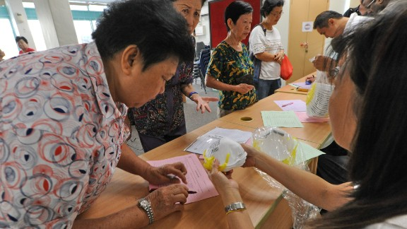 Elderly people sign up to collect face masks at the community centre for the low income in Singapore on June 22, 2013.