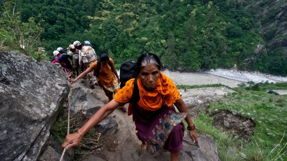 Stranded Indian pilgrims make their way up a mountain in Govindghat on June 23.