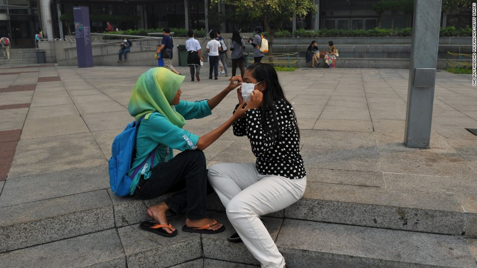 A woman helps her friend with a face mask as haze shrouds Kuala Lumpur on June 23.