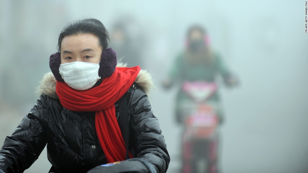 A woman rides a bike in the heavy smog with a mask on a street in central China's Anhui province in January 2013. Greenpeace released a 2013 report claiming that 83,500 people died prematurely in 2011 from respiratory diseases in Shandong, Inner Mongolia and Shanxi -- China's top three coal-consuming provinces.