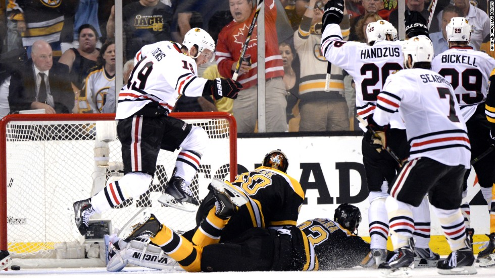 Jonathan Toews of Chicago, left, celebrates after scoring a goal against Boston.