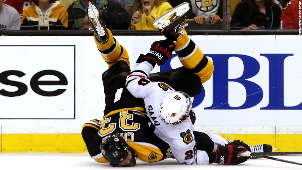 Zdeno Chara of the Boston Bruins and Brandon Saad of the Chicago Blackhawks fall to the ice.