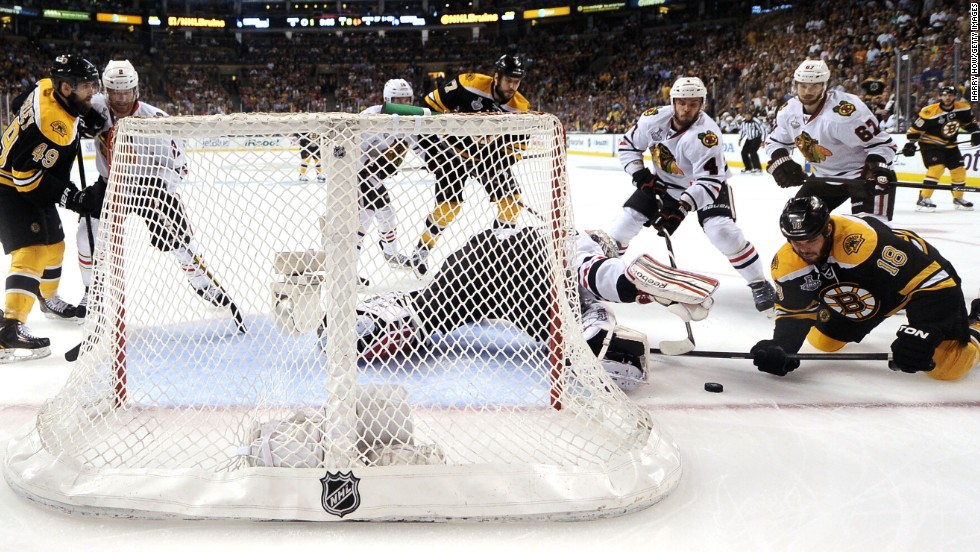 Goaltender Corey Crawford of the Chicago Blackhawks makes a save against No. 18 Nathan Horton of the Boston Bruins.